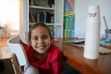 Five-year-old Amity, sits at her desk, smiling into the camera