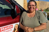 Carol Martin leans up against a red 4WD with her election poster on the side.