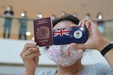 A woman holds a British National Overseas passport and a phone with the HK flag on it while wearing a pink hello kitty face mask