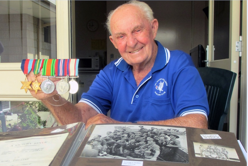 Len Snell with his medals and an album of photographs taken during the war with a box camera given to him by his mother.