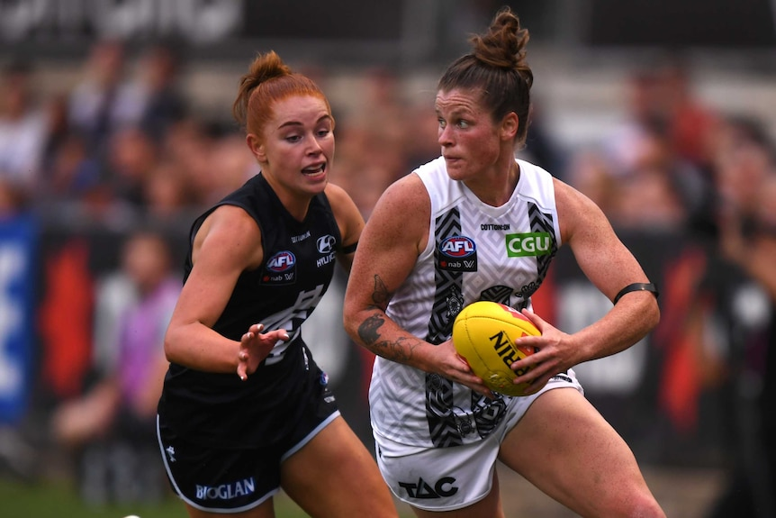 A Collingwood AFLW player runs with the ball in two hands in front of a Carlton opponent.