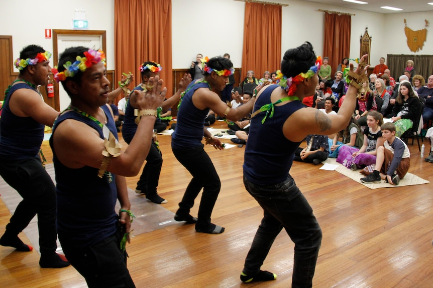 Kiribati dancers dressed in traditional colourful clothing dance for a crowd