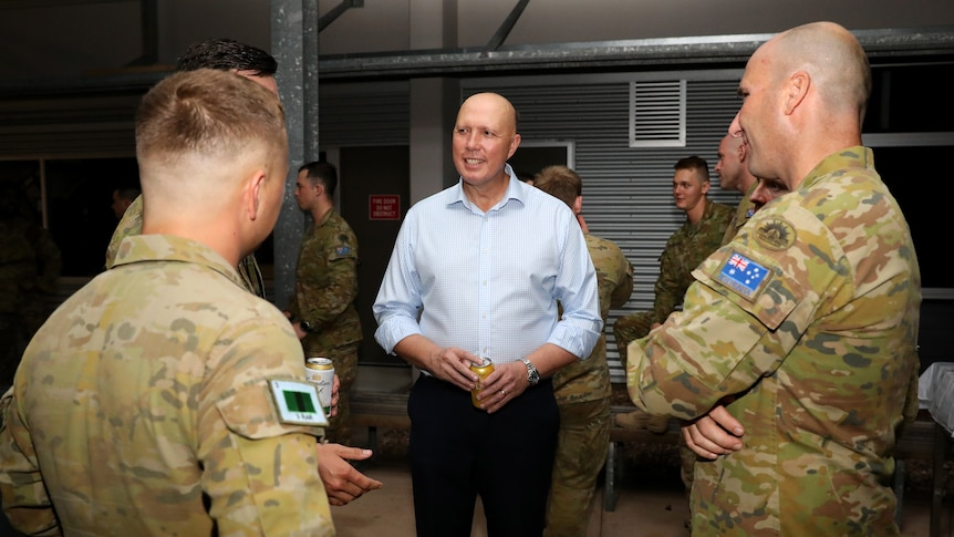 A bald man wearing a blue shirt stands talking to two soldiers dressed in army uniforms