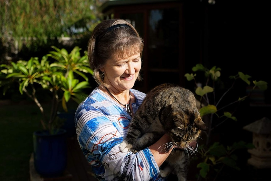 A woman holding her cat looking down at it.