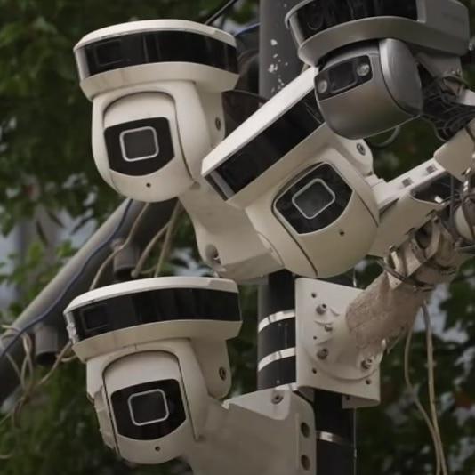 A group of surveillance cameras on a pole.