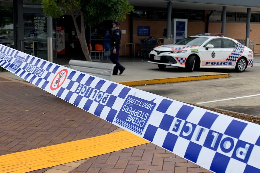 Police tape, police car and police officer outside Aldi supermarket where girl was shot with bow and arrow
