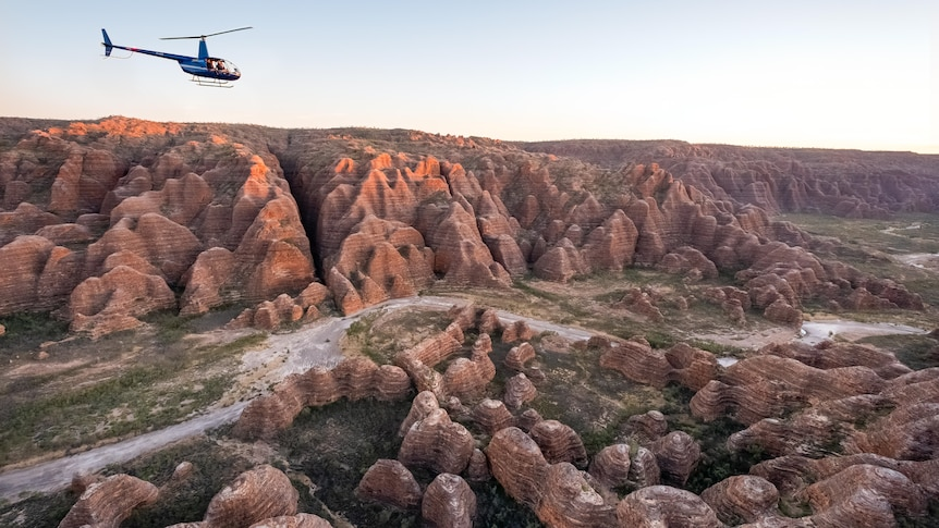 helicopter flies above beehive-like  rock formations