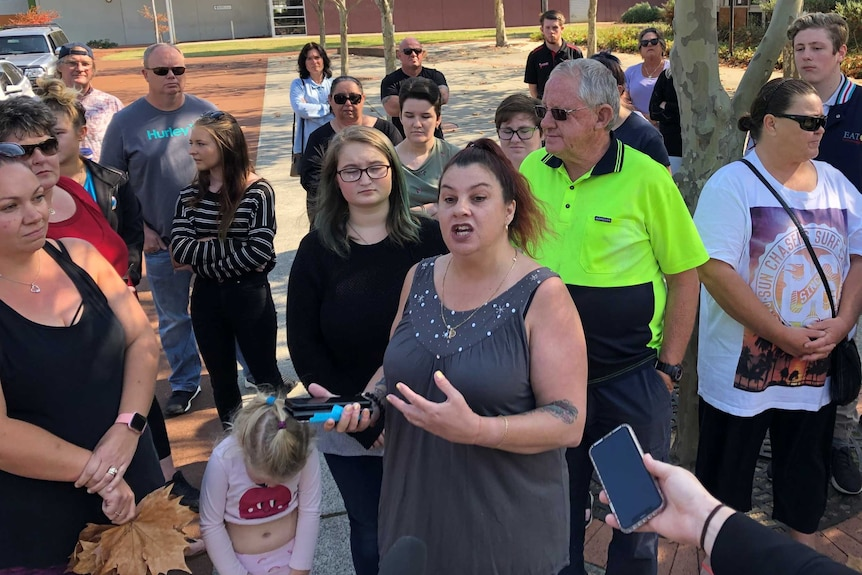 A woman standing in a group of about 20 people speaking in protest,  in Eaton.