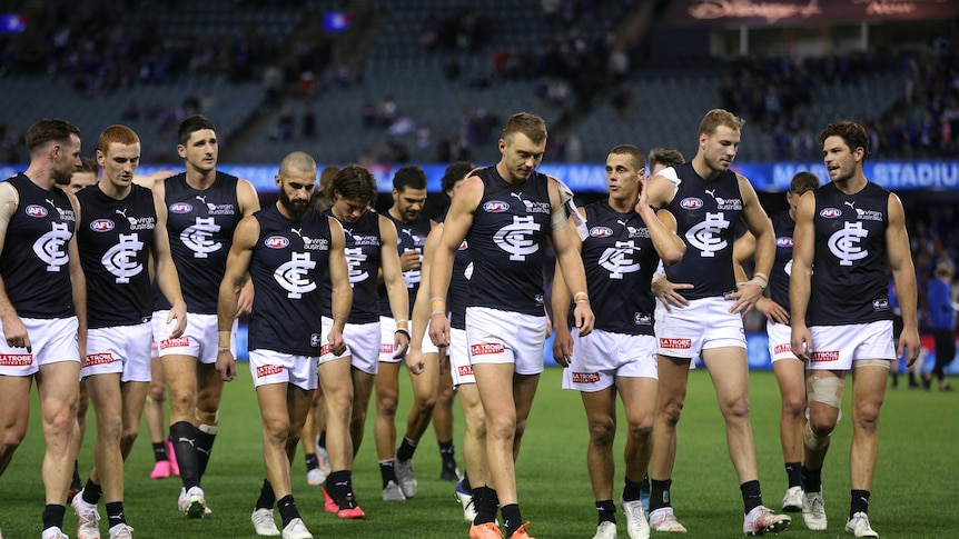 A dejected group of AFL players walk off the ground after a loss.