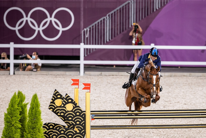 A man rides a horse that is jumping over a jump in an arena with photographers in the background
