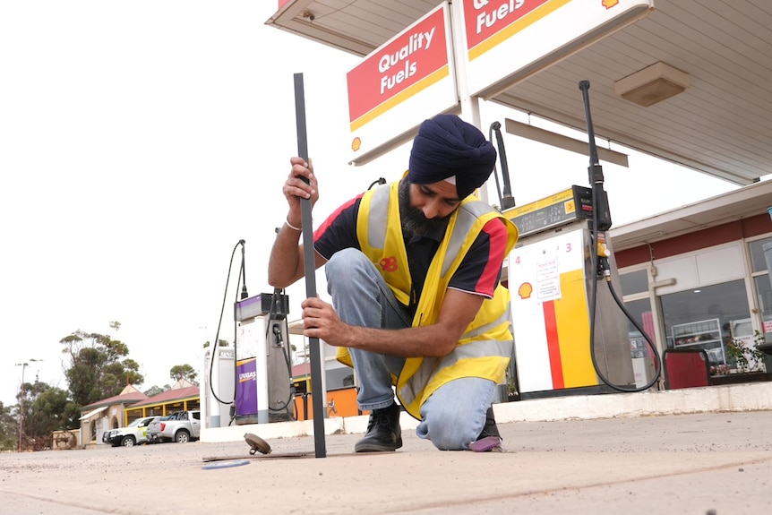 An Indian man holding a long rod pulled from underground fuel tank at a service station