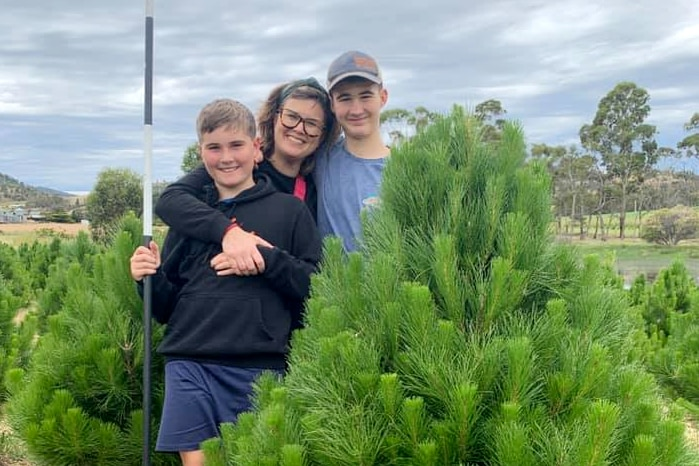 A mother and two sons hugging and smiling, behind a Christmas tree
