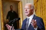 Biden gestures while giving a speech in front of an old portrait