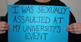 """A person holds a blue poster with the words 'I was sexually assaulted at my university's event""""."""