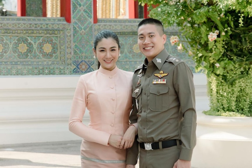 A young Thai woman in a traditional chut thai, and a man in a green police uniform
