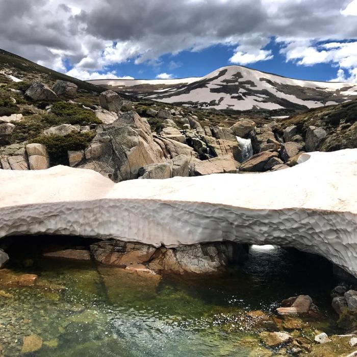 A creek flows between a snowy bridge on a mountain side.