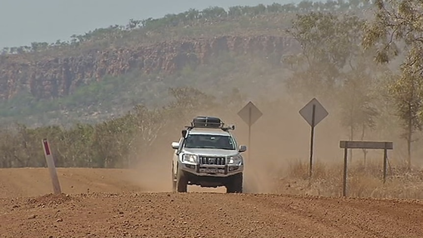 A 4 wheel drive vehicle on a gravel road.