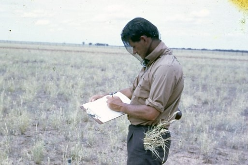 A man stands in a paddock writing on a notebook