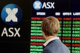 A man, seen from behind, looks at the ASX share price boards.