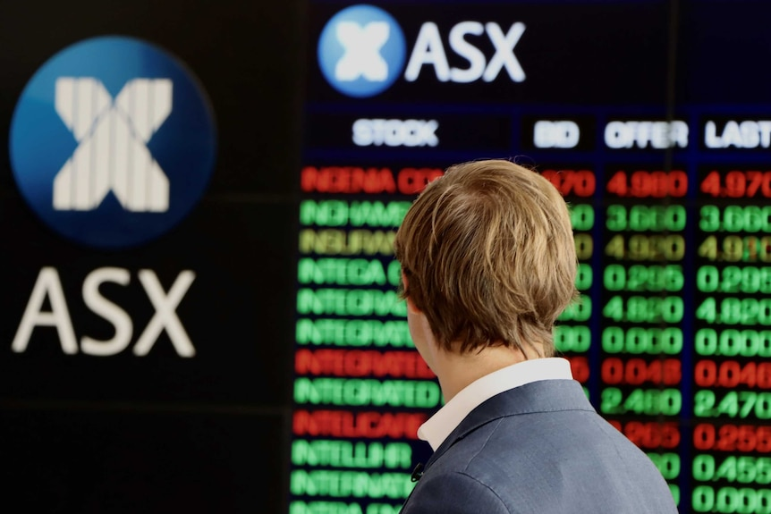 A man in a suit, seen from behind, looks at the ASX share price boards.