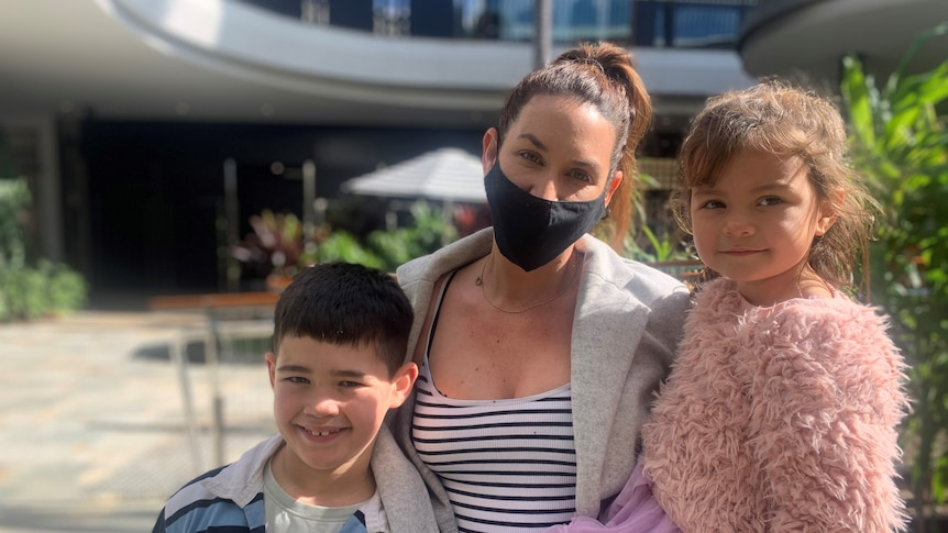 Mother in a mask and her two kids standing together