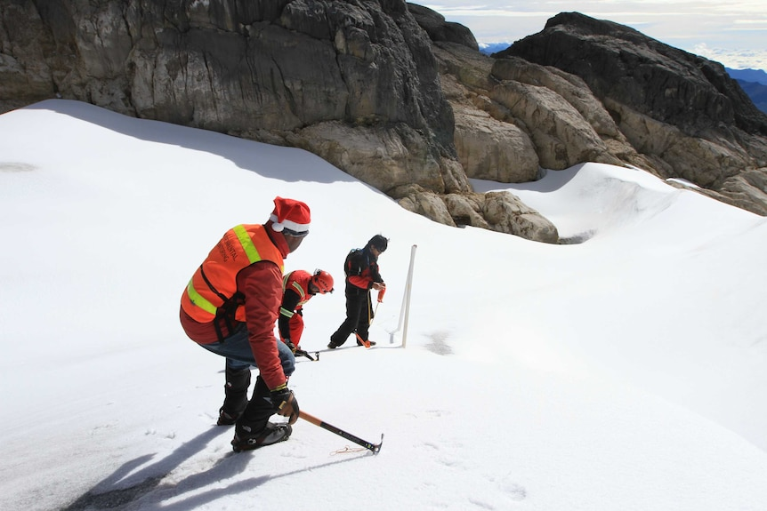 Three people, one wearing a santa hat, stand on sloping ice on a mountain. One is setting up equipment.