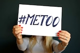 A woman holds a sign with the words #MeToo.