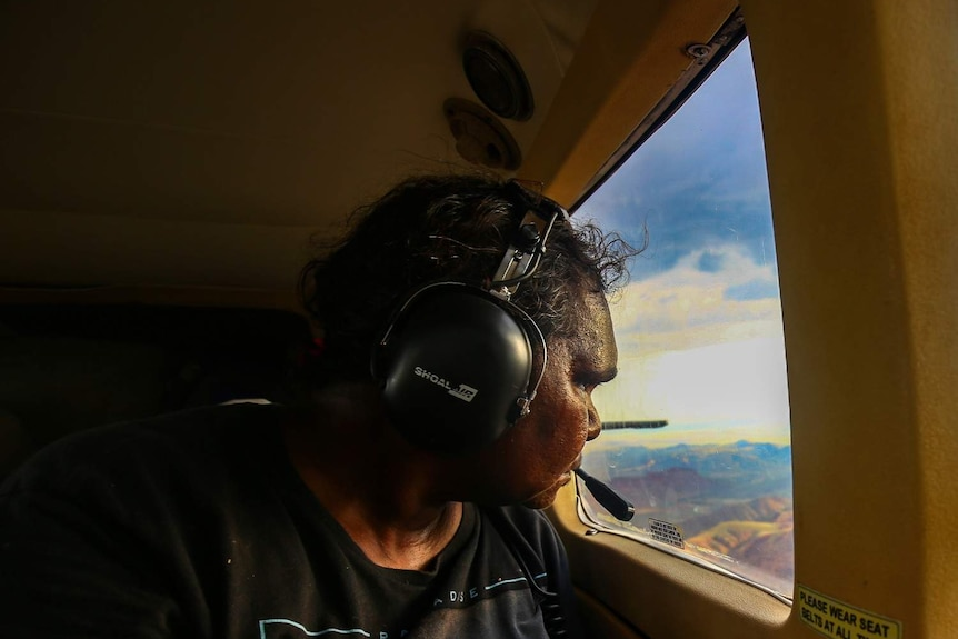A woman wearing a black tshirt and a headset looks out a plane window.