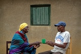 Genocide survivor Laurencia Mukalemera, left, a Tutsi, is offered a cup of water by Tasian Nkundiye, a Hutu