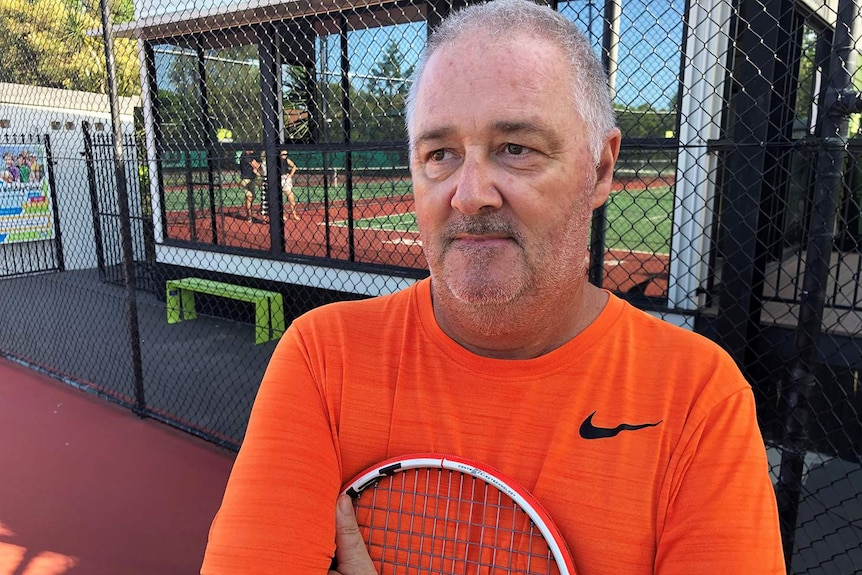 Headshot of Clive Martin holding a tennis racket close to his chest.
