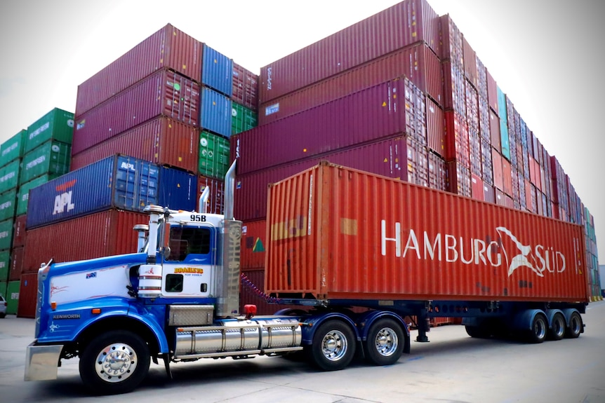 A truck carries a Hamburg Sud shipping container in front of a stack of other containers at Sydney's Port Botany.