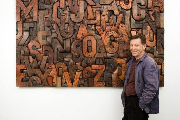 A man stands in front of a large wood carving artwork of jumbled letters