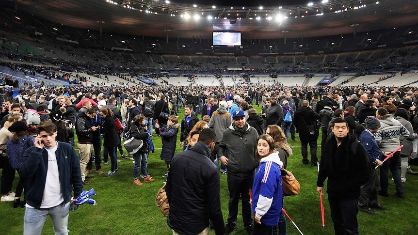 Spectators gather on the pitch after France-Germany international soccer match at Stade de France.