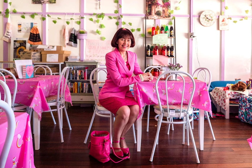 A woman wearing all pink sits in a cafe with pink table clothes.