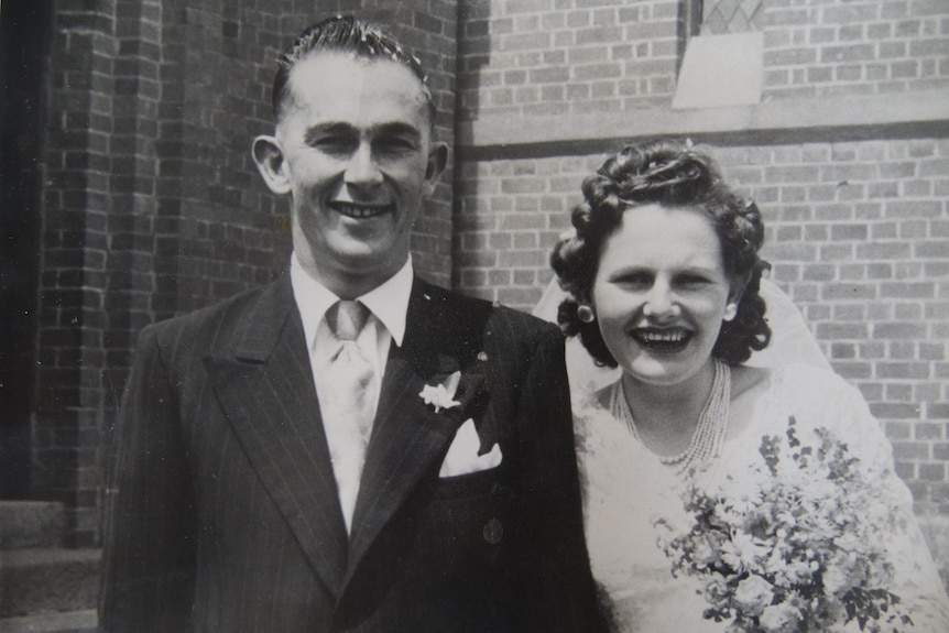 An historic black and white photo of a bride and groom grinning out the front of a touch