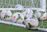 Several soccer balls lie inside the goal posts.