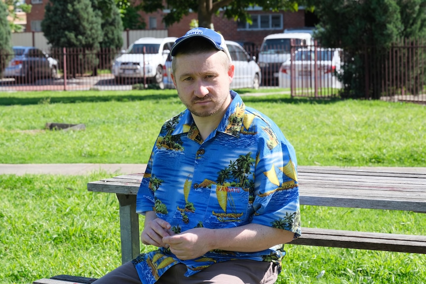 A young man sits on a park bench wearing a blue cap and a Hawaiian shirt.