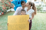 Couple kissing in front of pregnancy announcement