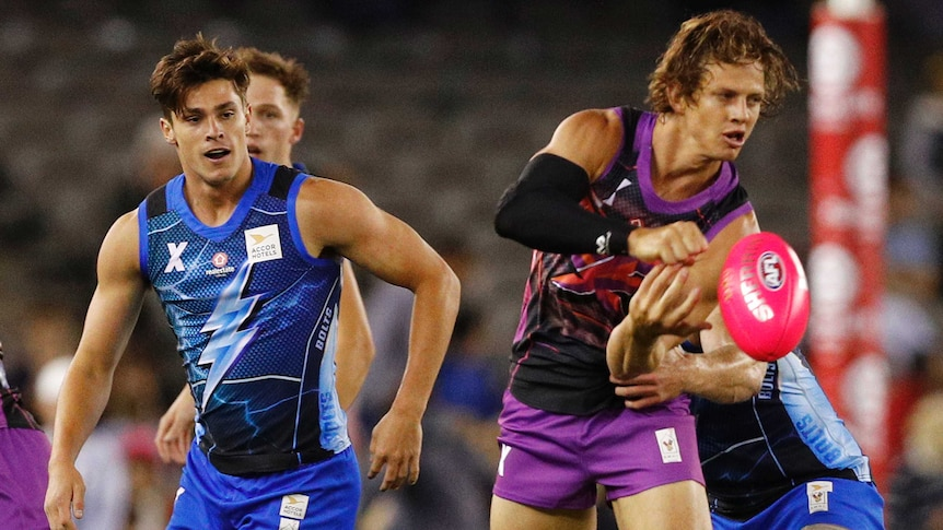 Nat Fyfe looks to handpass during an AFLX exhibition game as an opponent looks on behind him