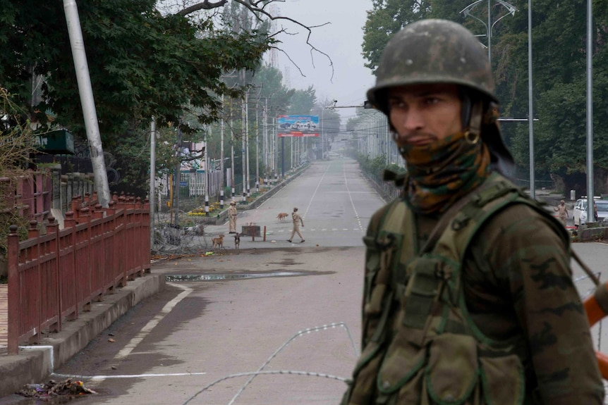 An Indian paramilitary soldier stands guard on a deserted road leading towards an Indian Independence Day parade in Kashmir.