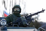 A military personnel member, believed to be a Russian serviceman, stands guard on a military vehicle