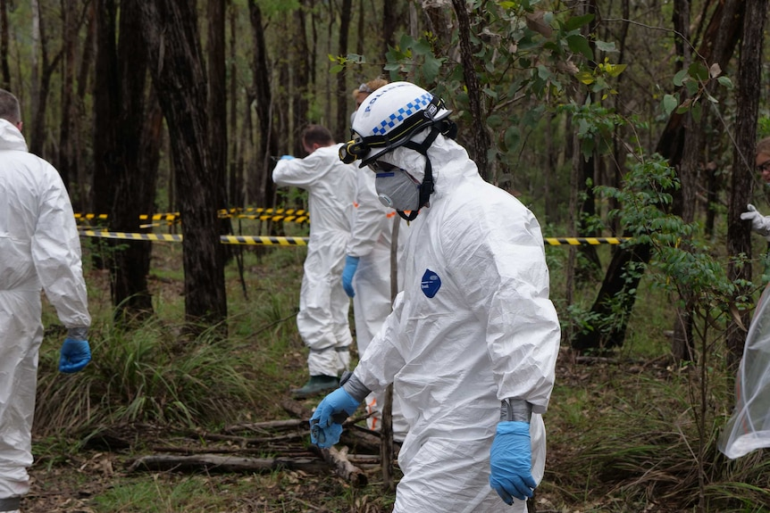 A forensic police officer walks through bushland at the AFTER facility near Sydney, February 2020.