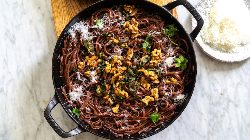 A wide pan filled with red wine pasta topped with sage, brown butter and walnuts, an easy vegetarian one pot meal.