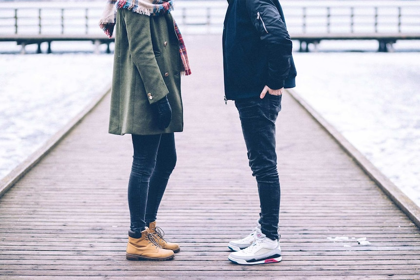 Couple standing slightly apart on a pier on an overcast day