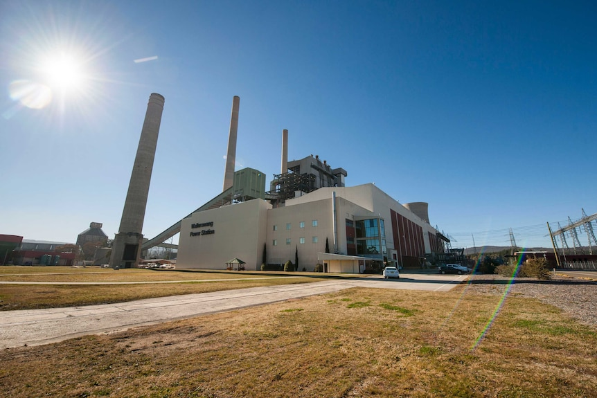 A wide-angle photo of a disused power station, with large white buildings and smokestacks.