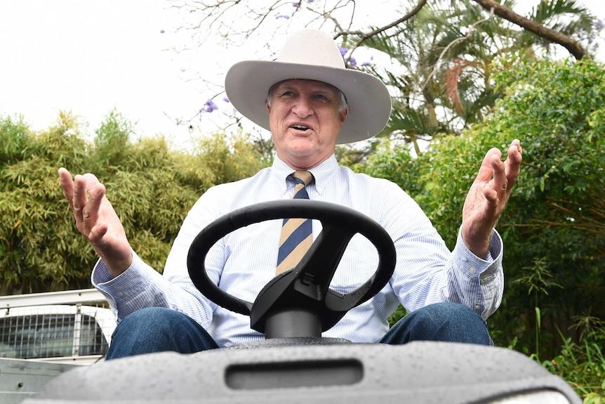 Akubra-clad Bob Katter on a ride-on mower