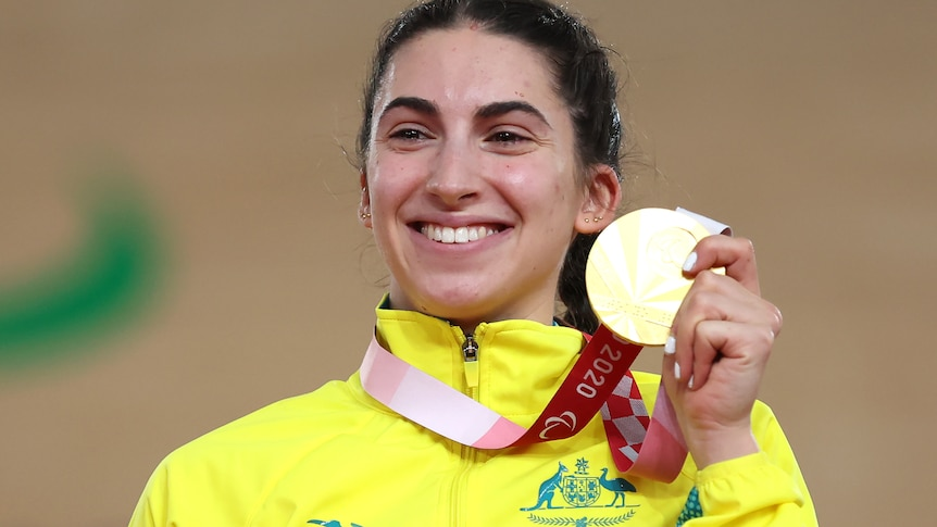 Paige Greco holds her gold medal and smiles