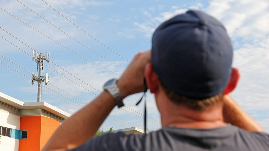 A man peers through binoculars at a telecommunications tower across the road.