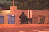 Police crouch near a building in Brighton