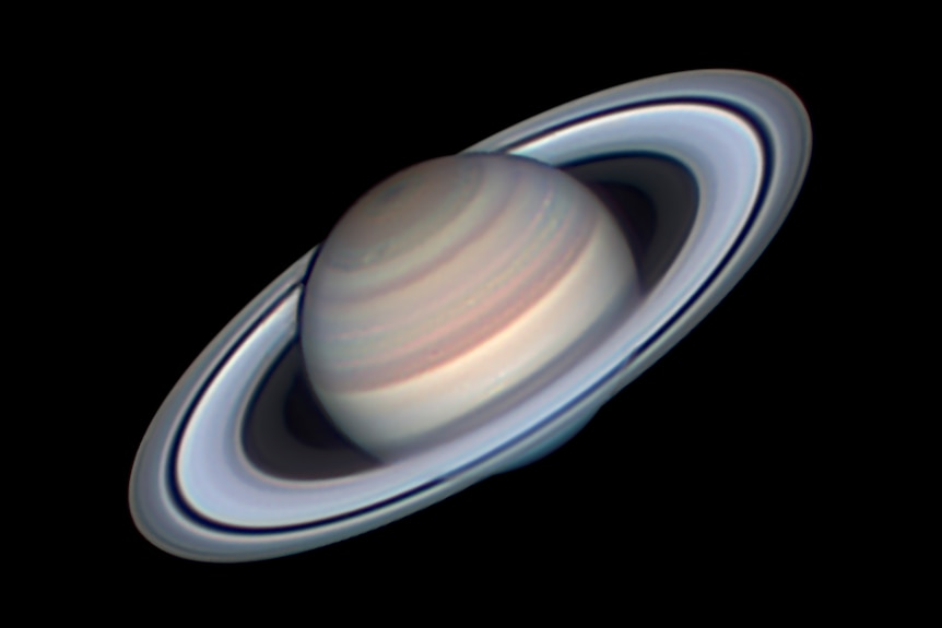 A black background with a circular planet and symmetrical rings,